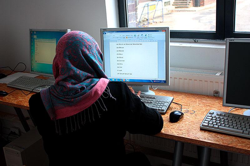 Frau von hinten am Computer, Digital Empowerment Training für geflüchtete Frauen in einer Unterkunft