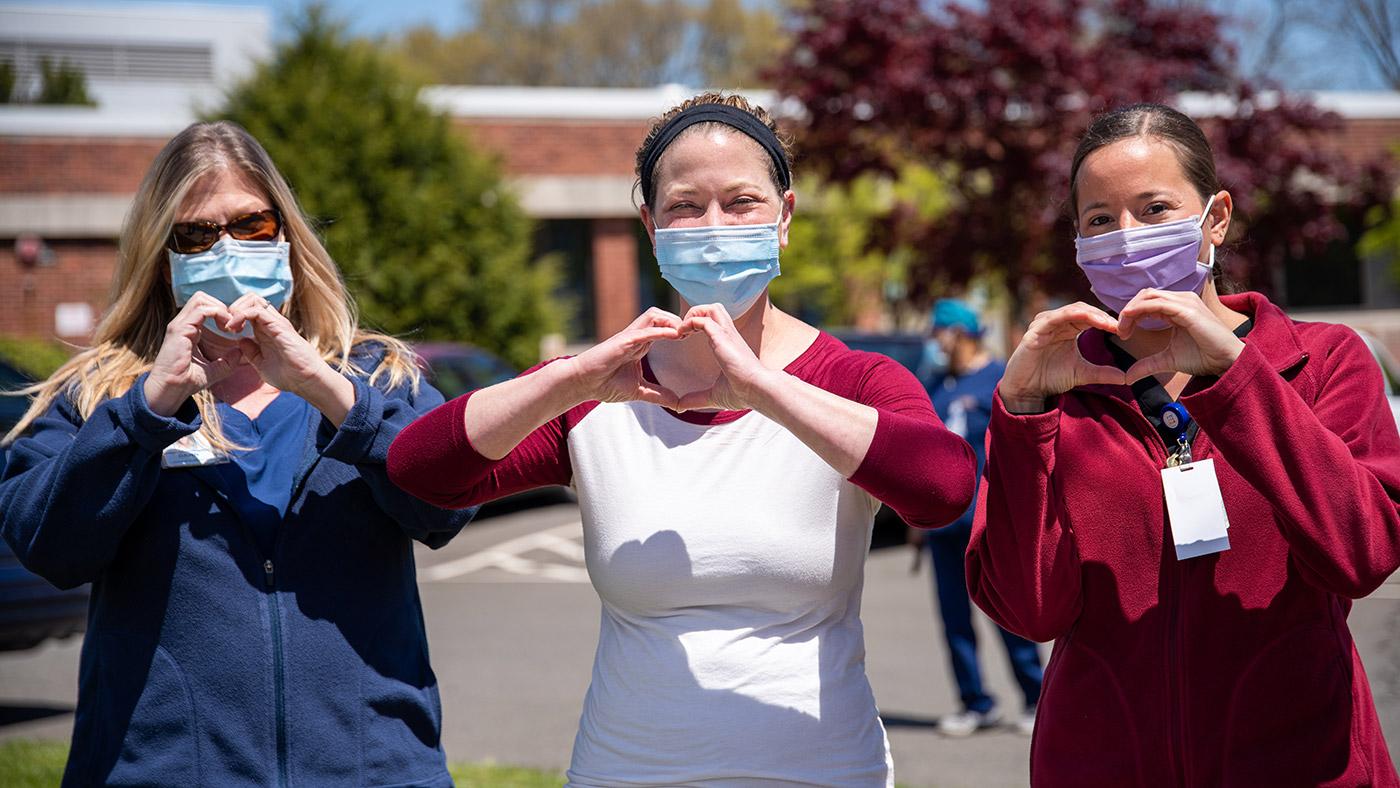 Symbolbild (Drei Pflegekräfte zeigen Hand-Herz-Zeichen) ©Rusty Watson/Unsplash